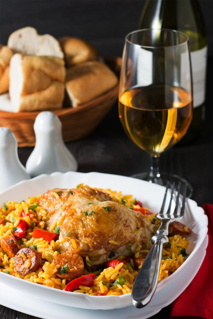 A close up of the golden chicken on the yellow saffron rice with slices of sausage and red peppers