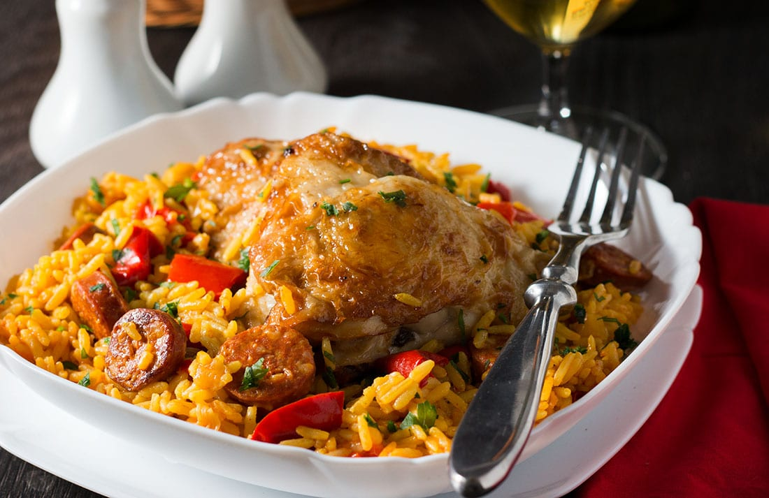 Colorful Chicken & Chorizo Paella in a white dish with a fork beside it.