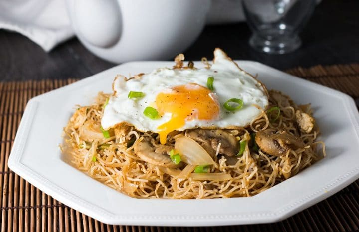 Stir fried rice noodles with vegetables topped with a fried egg with the yolk dripping into the noodles