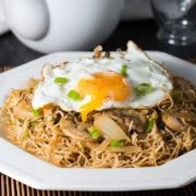 A plate of noodles with a fried egg on top and chopped green onions