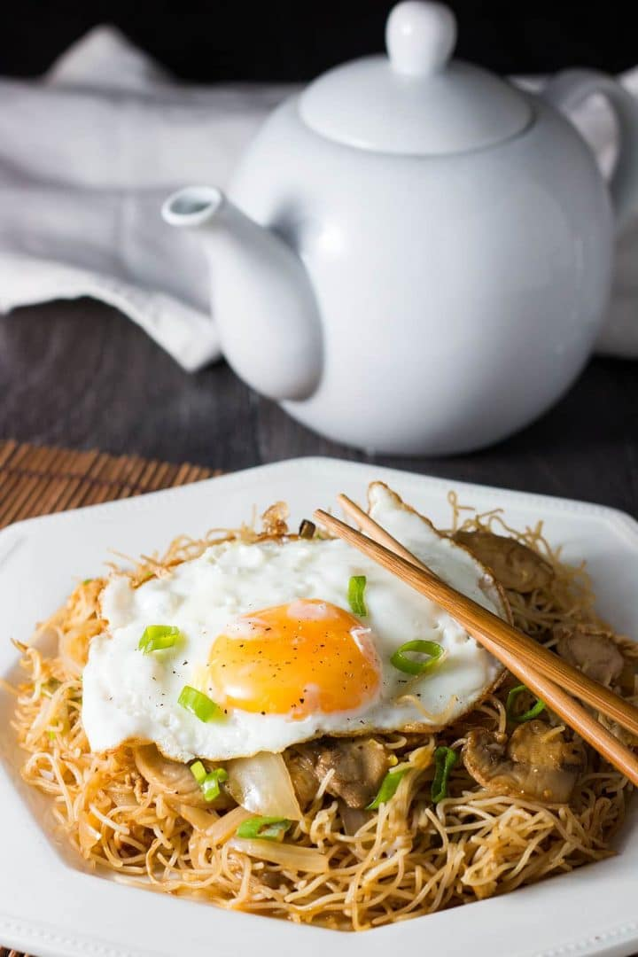 A white plate with stir fried rice noodles and vegetables topped with a fried egg and sprinkled with green onions and chopsticks laying on the plate