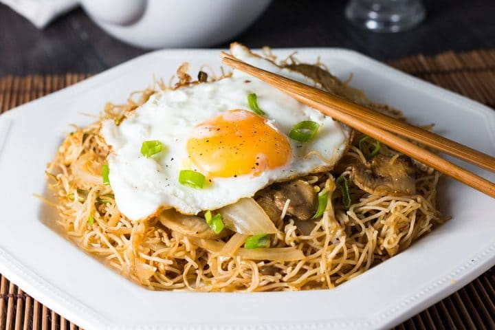 a close up of the Fried Eggs with Chinese Noodles with chopsticks on the plate and garnished with sliced green onions.