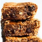 A close up of a stack of Oatmeal cookie bars with soft centers