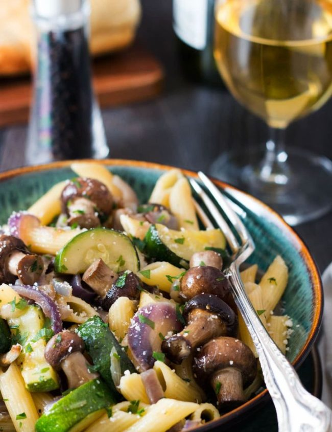 A close up of a bowl of pasta with roasted red onions, mushrooms and zucchini