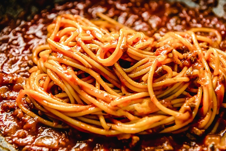 spaghetti added to the sauce in the pan