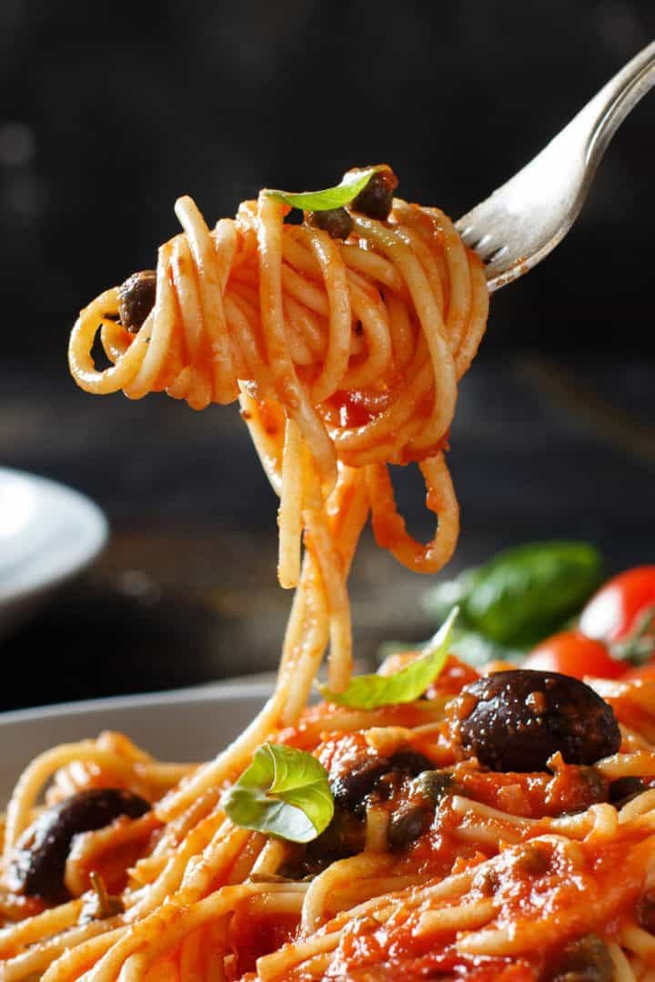 Spaghetti Alla Puttanesca twirled on a fork over the plate