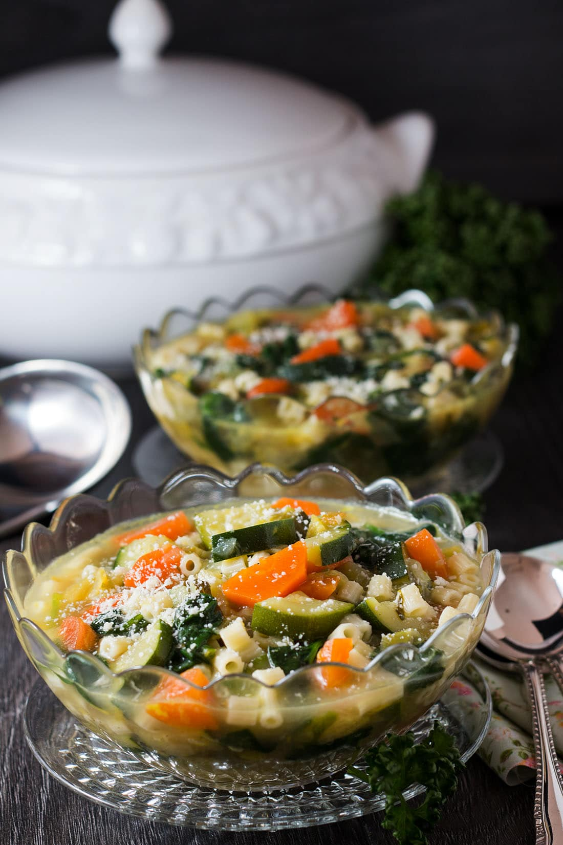 Two bowls of Spring Vegetable Soup in glass bowls with cultery