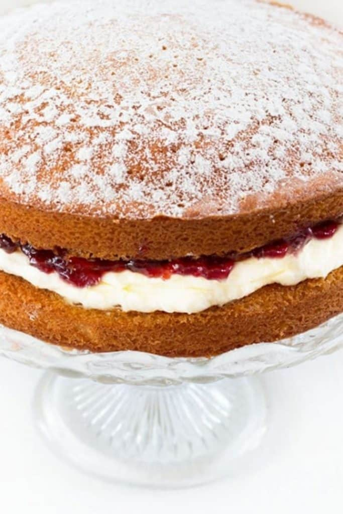 Victoria Sponge Cake with Whipped Cream and jam on a cake stand