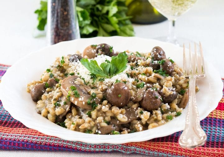 A close up of Skinny Mushroom & Barley Risotto topped with parsley and grated cheese.