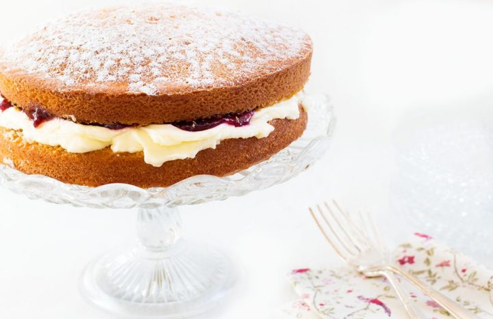 Classic Victoria Sponge Cake on a glass cake stand with a floral napkin and a silver fork next to it
