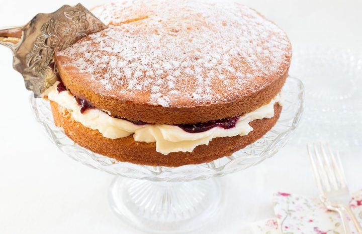 Victoria sponge cake on a cake stand with a cake slice, slicing through
