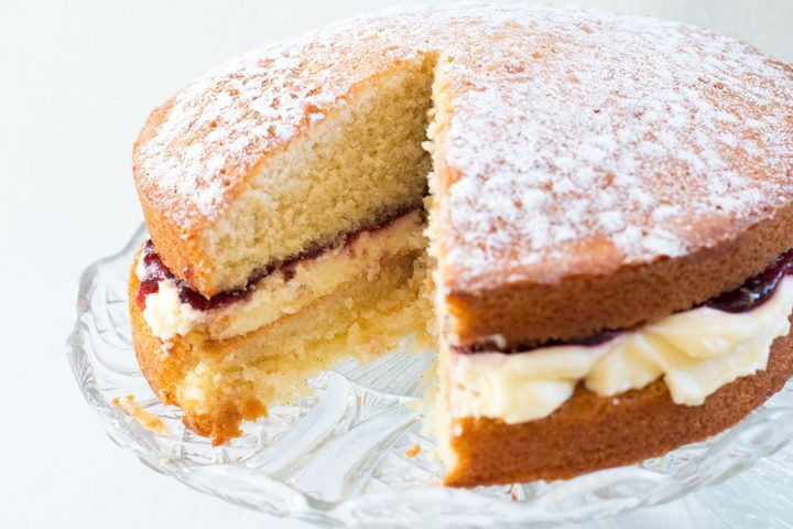 Classic Victoria Sponge Cake with a piece missing on a glass cake stand
