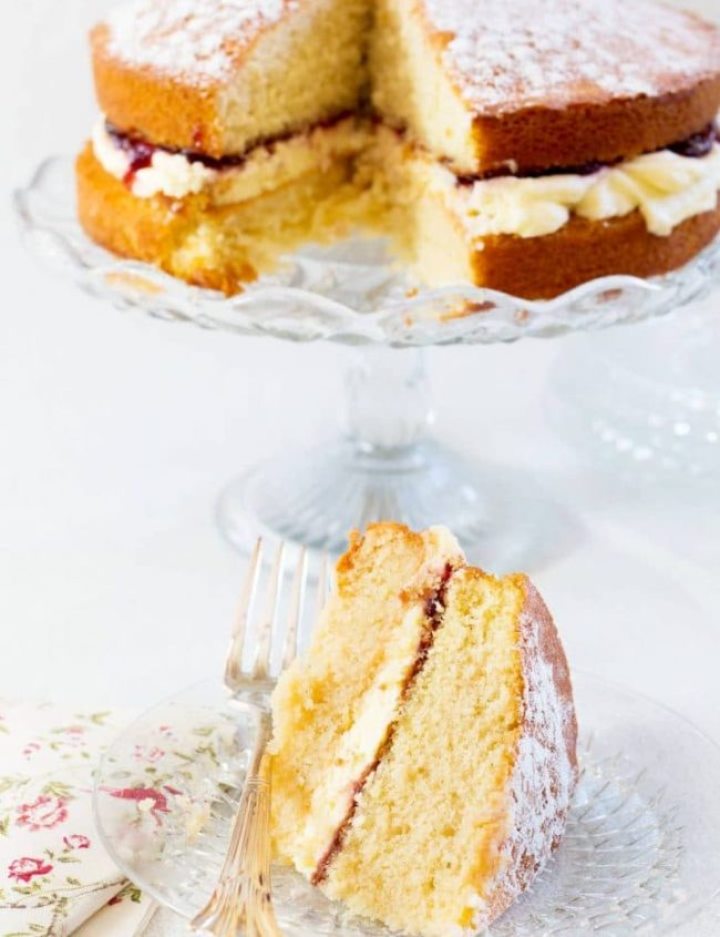 Victoria Sponge Cake filled with buttercream and strawberry jam on a cake platter