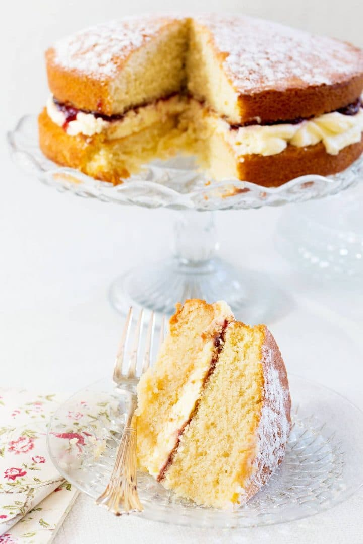 Classic Victoria Sponge Cake slice on a glass plate with fork and floral napkin with the remaining cake on a glass cake stand in the background