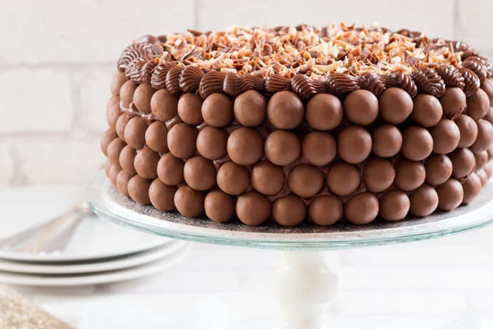 A Chocolate cake covered in malted chocolate balls and chocolate curls on a cake stand with plates and forks behind it.