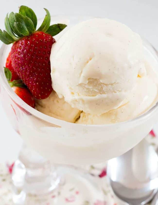 Easy No Churn Vanilla Bean Ice Cream in a stemmed dessert bowl with a strawberry
