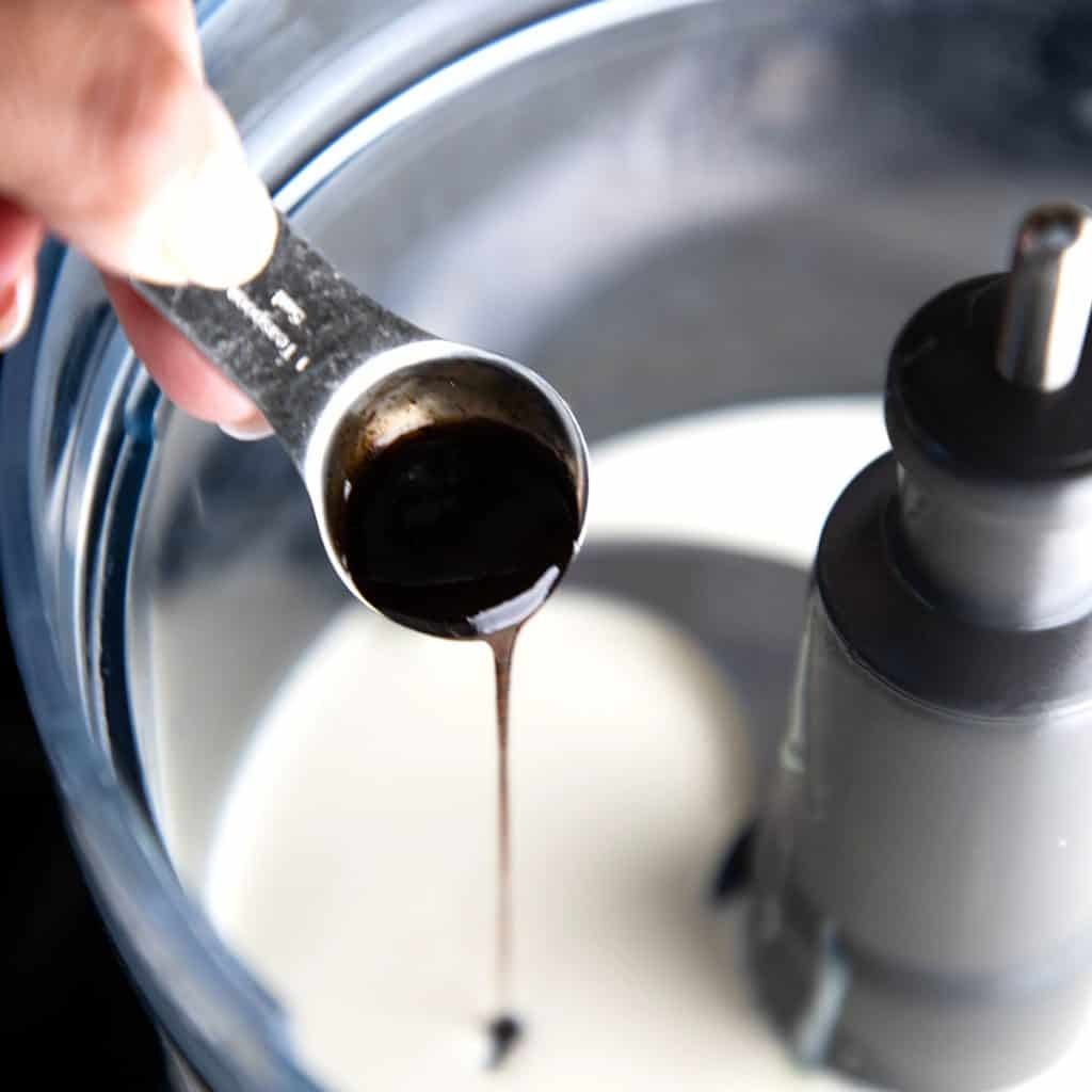 vanilla bean paste being added to cream and condensed milk in a bowl