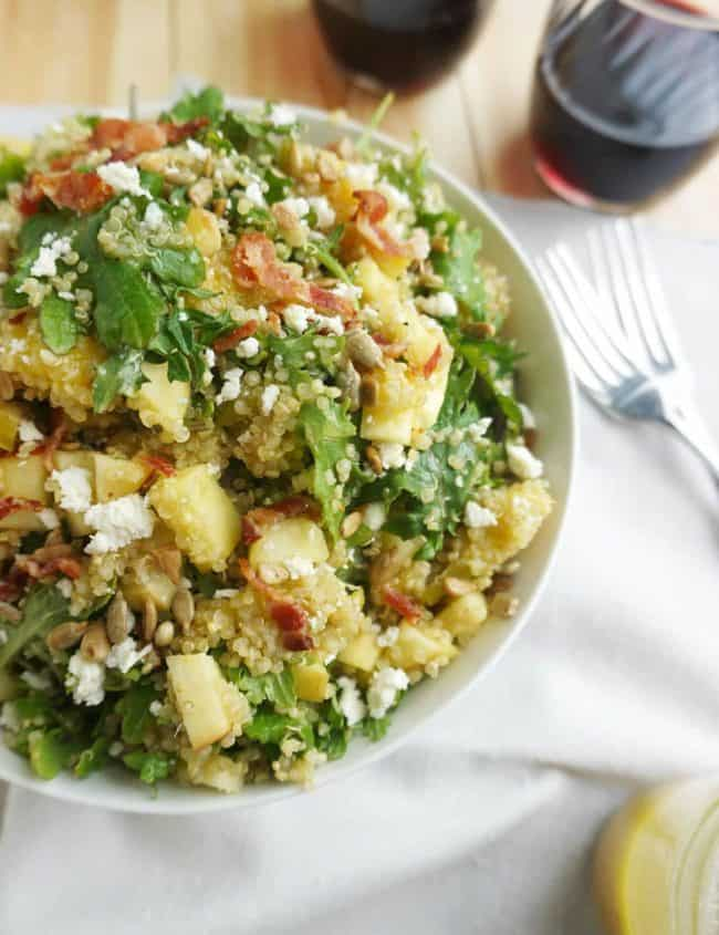 Bacon Quinoa Salad with Lemon Dijon Dressing piled high in a bowl with a fork next to it