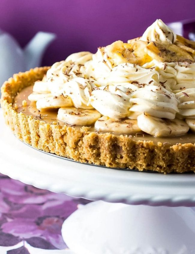 The Banoffee Pie on a cake stand showing the crust, caramel layer, banana layer, whipped cream and banana chips as decoration