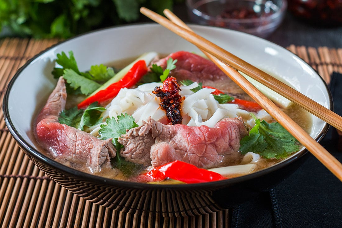 Tuan's Vietnamese Beef Noodle Pho in a black bowl with chop sticks