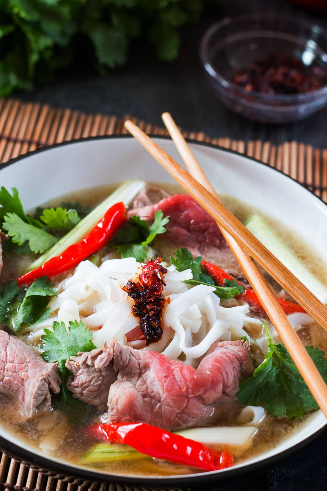 Tuan's Vietnamese Beef Noodle Pho in a bowl with chop sticks and garnish