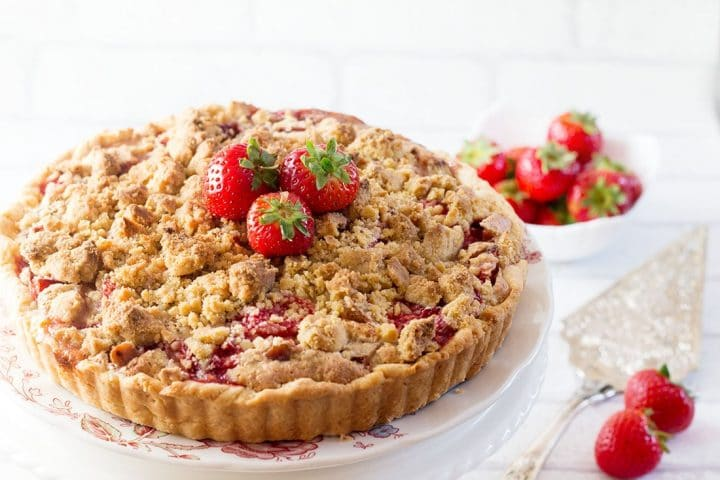 A Rhubarb and Strawberry Crumb Pie topped with a golden, crunchy crumb topping and fresh strawberries as garnish.