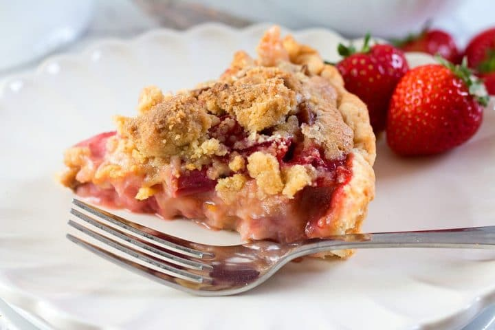 a piece of Rhubarb and Strawberry Crumb Pie sitting on a plate with a fork and more strawberries in the background