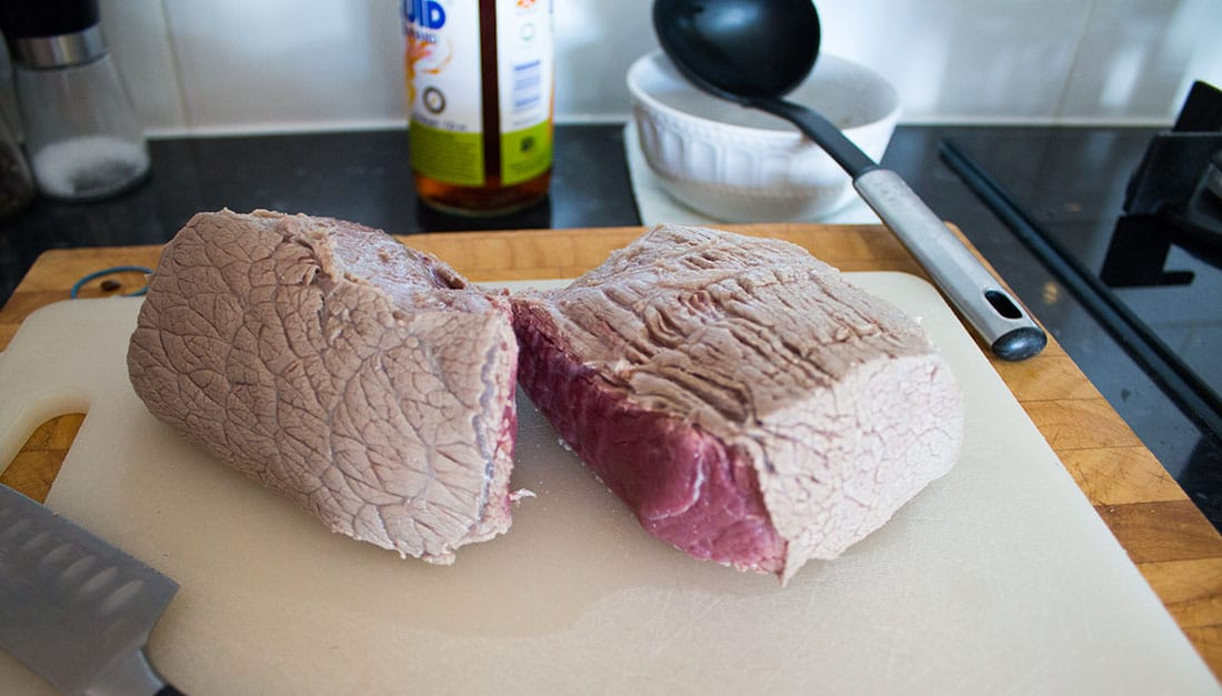 rare cooked beef joint cut in half on a white chopping board