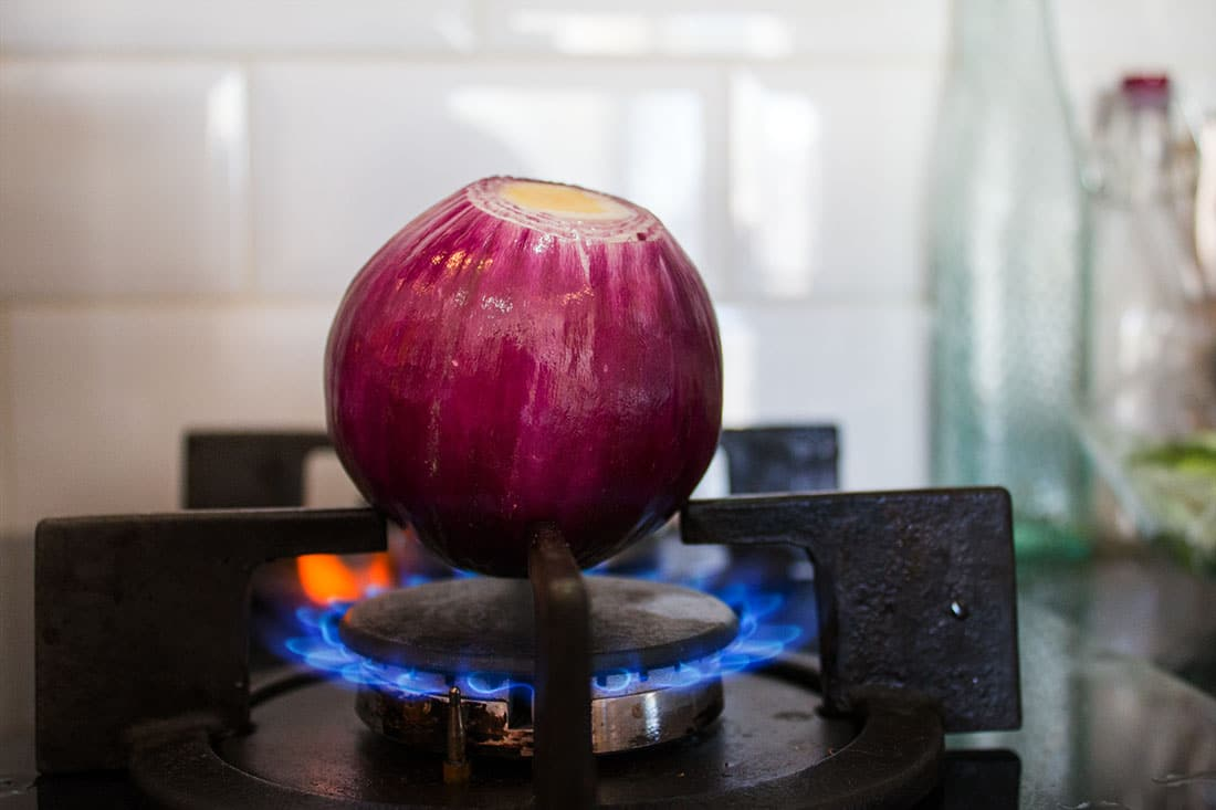 a whole peeled red onion roasting on a gas ring