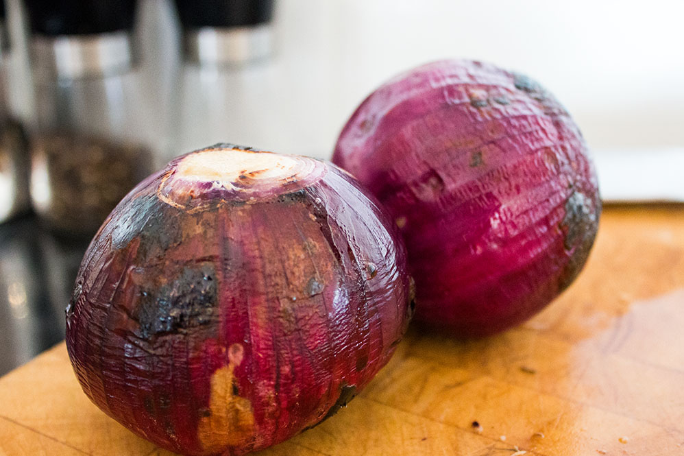 two freshly roasted red onions on a wooden cutting board