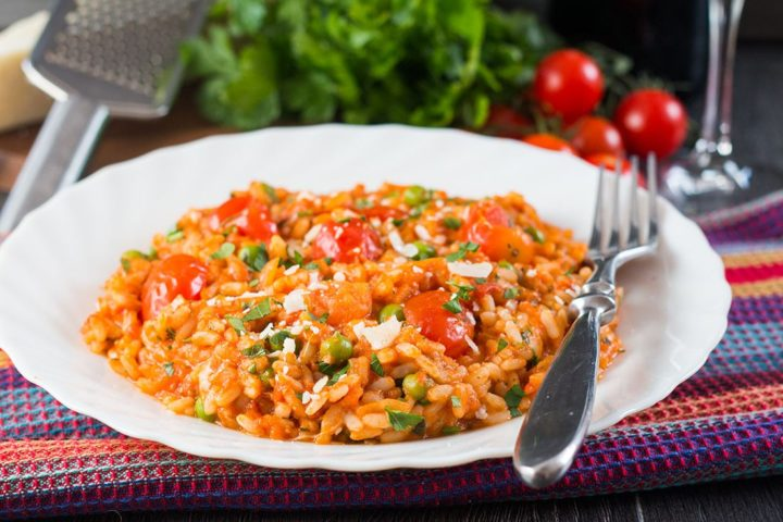 Roast Tomato and Pea Risotto on a white dish with a fork