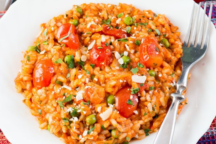 A plate of roast tomato and pea risotto sprinkled with parmesan