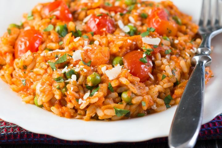 close up of a bowl of Roasted Tomato and Pea Risotto with a fork