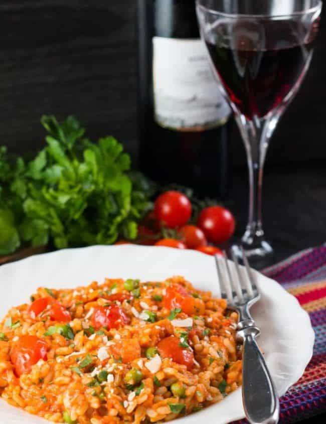 A plate of roast tomato and pea risotto with a glass of red wine and ingredients in the background