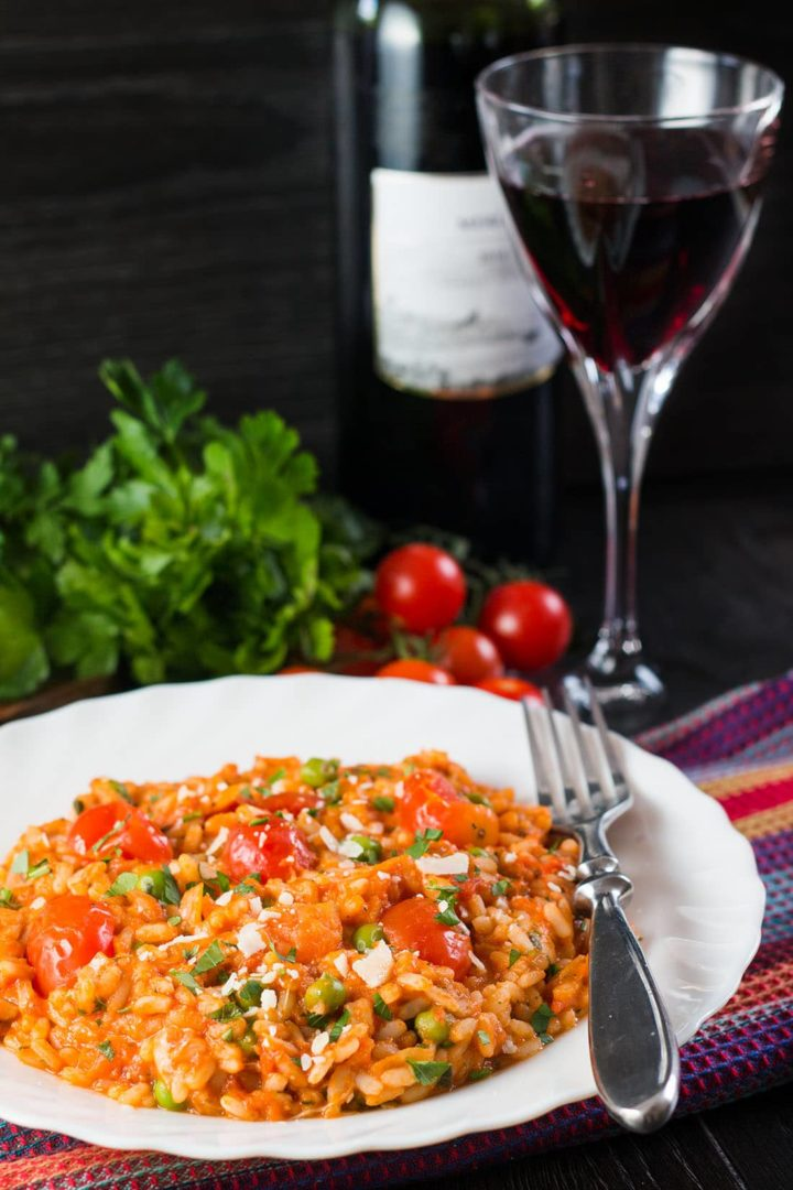 Roast Tomato and Pea Risotto in a dish with a fork and a glass of red wine, bottle of red wine and tomatoes and herbs in the background