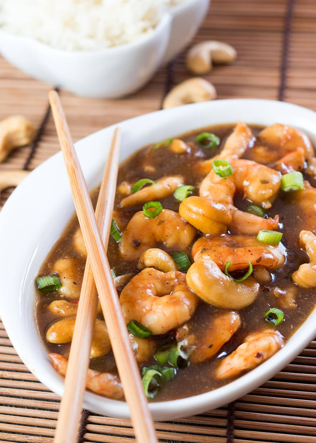 Cashew shrimp in a bowl with a bowl of fluffy rice in the background