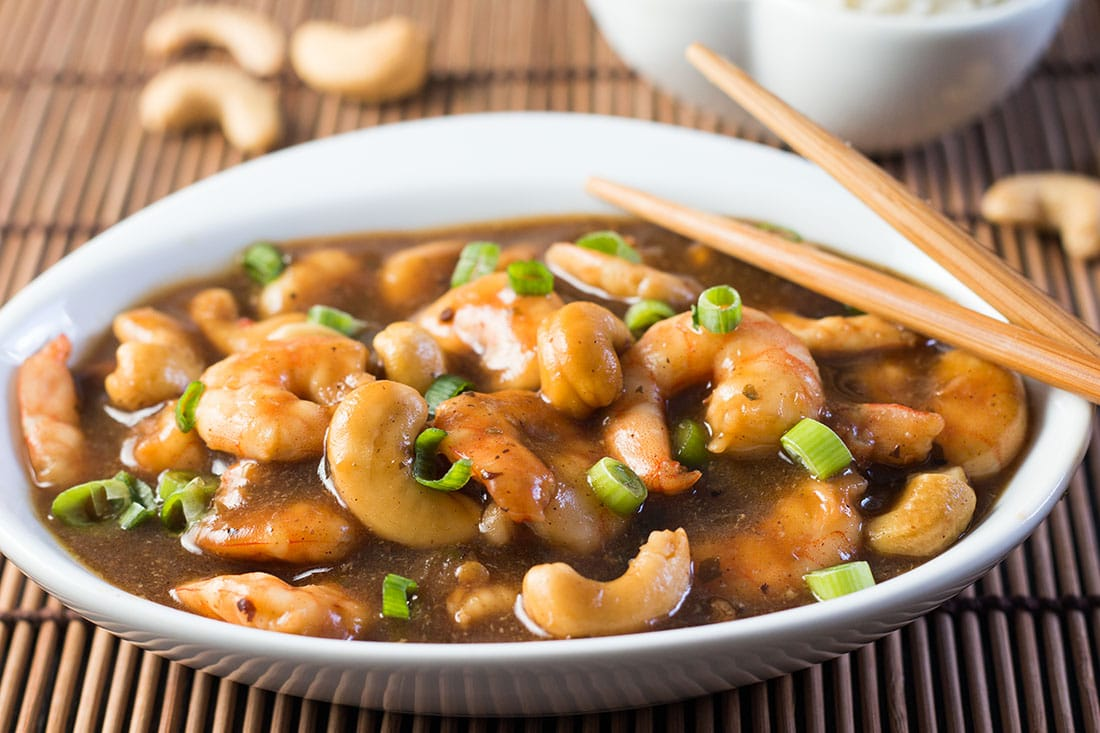A bowl of cashew shrimp on a bamboo mat.