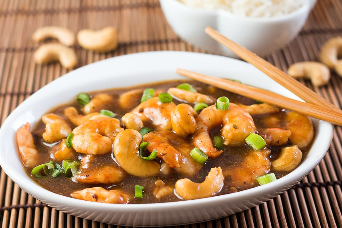 Cashew shrimp in a bowl with chop sticks beside it