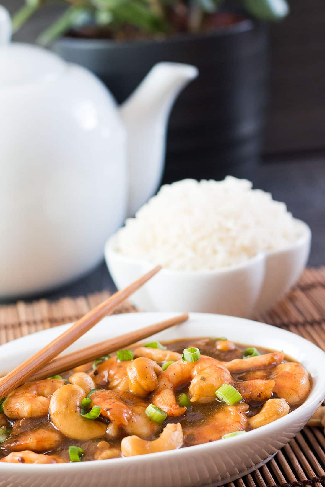 Cashew shrimp, rice in a bowl with a white teapot in the background.