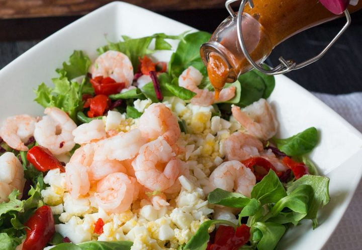 Shrimp and Egg Salad in a square white bowl with dressing in a bottle being drizzled over