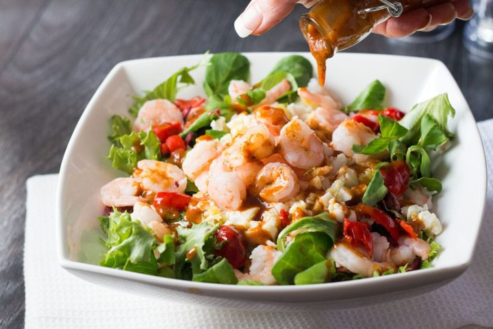 shrimp salad in a white square bowl with dressing being drizzle over it