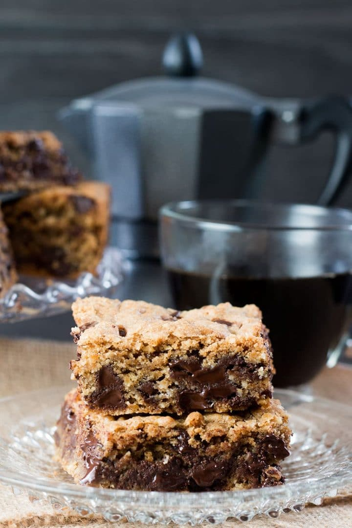 2 Chocolate Chip Spiced Oatmeal Cookie Bars on a crystal plate with a cup of coffee in the background