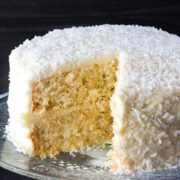 coconut lovers dream cake on a plate with a piece cut from it