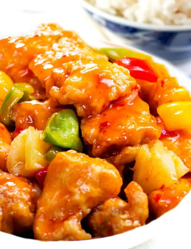 a bowl full of Sweet and sour chicken with white rice in the background