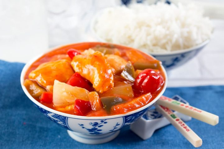 Sweet and Sour Chicken in a blue and white patterned bowl with chopsticks resting next to it and a bowl of rice in the background