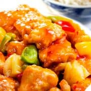 a close up of a bowl full of Sweet and sour chicken with white rice in the background