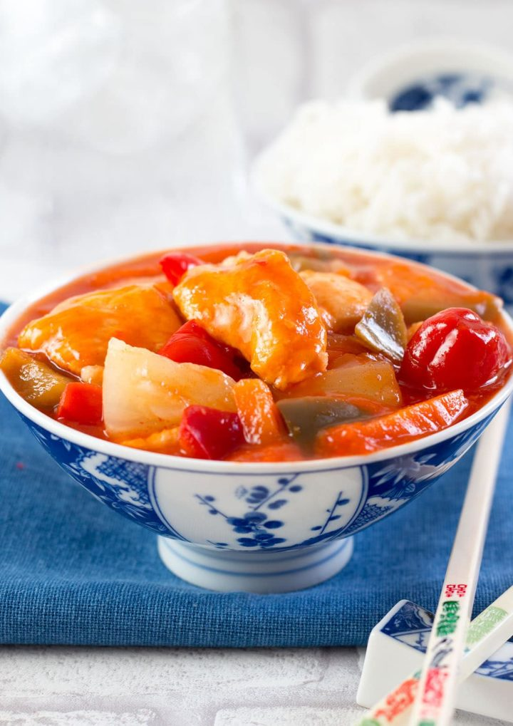 Sweet and Sour Chicken in a blue and white bowl with chopsticks and  rice in the background