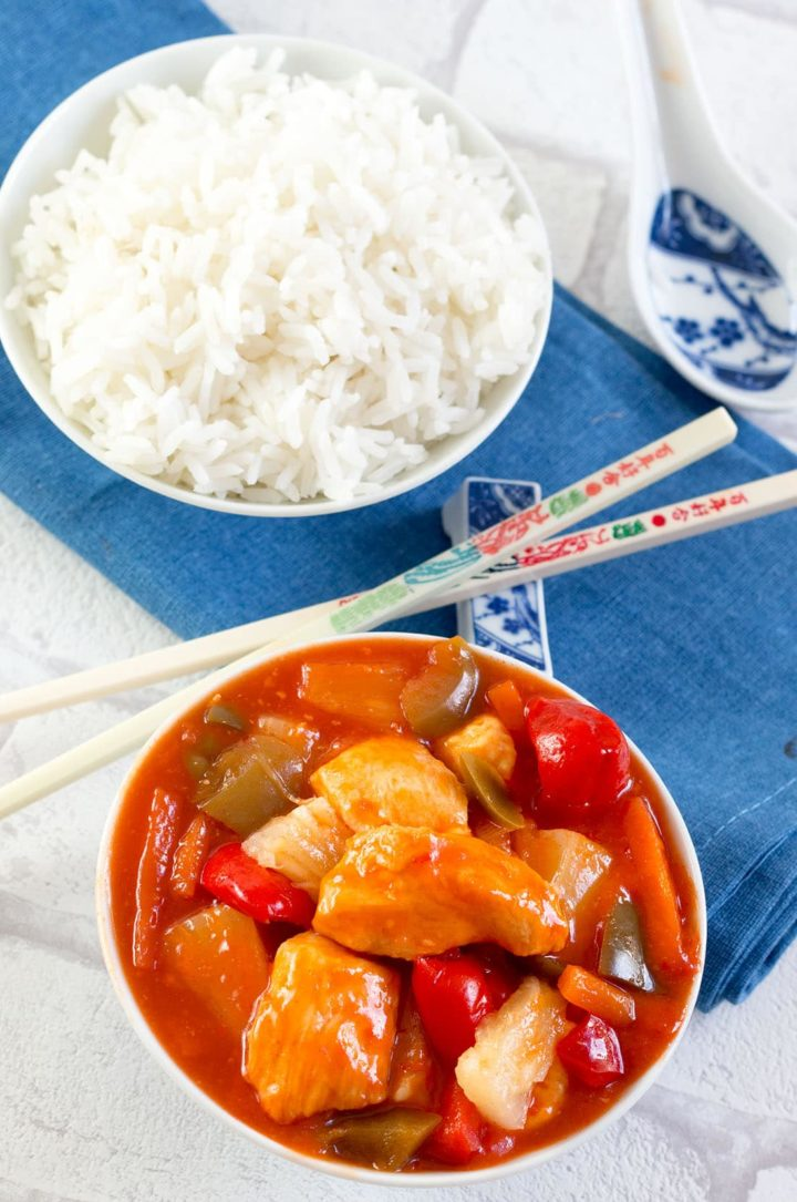 Sweet and Sour Chicken in a bowl and a bowl of white rice with chopsticks between them and a decorative sppon