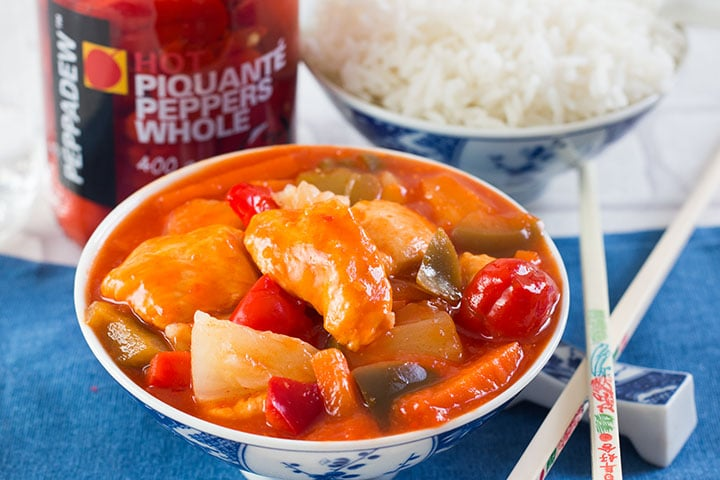 Sweet and Sour Chicken in a bowl with chopsticks and a bowl of rice, and jar of peppers in the background