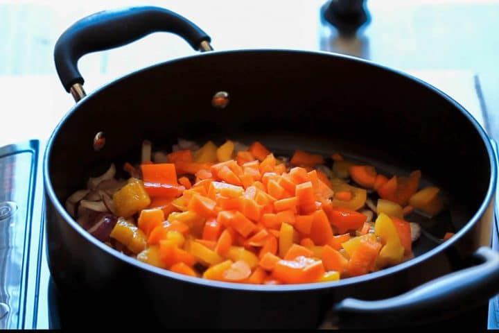 Diced carrot added to the pan with the peppers and onions